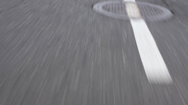 stockvideo's en b-roll-footage met wearable camera shot showing the view over road markings and manhole covers from a moving vehicle, long island, usa. - wegmarkering