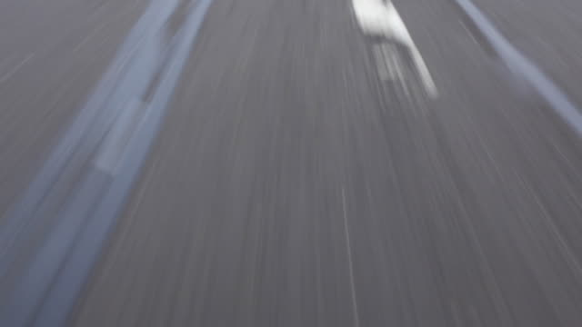vidéos et rushes de wearable camera shot showing worn and uneven tarmac from a moving vehicle, long island, usa. - macadam