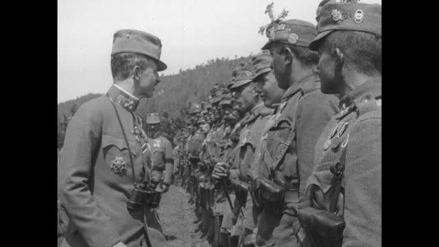 wearing a black arm band, austria's emperor charles i reviews troops, pats the shoulder of a young soldier; he salutes and chats with others / note:... - austria video stock e b–roll