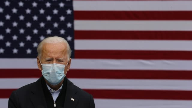 wearing a face mask to reduce the risk posed by the coronavirus, democratic presidential nominee joe biden delivers remarks in the parking lot of the... - human face stock videos & royalty-free footage