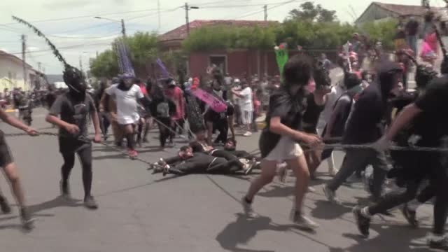 stockvideo's en b-roll-footage met wearing elaborate masks, nicaraguans chain and drag a mock judas through the streets of the southern city of masatepe, in an easter-time ritual... - judas
