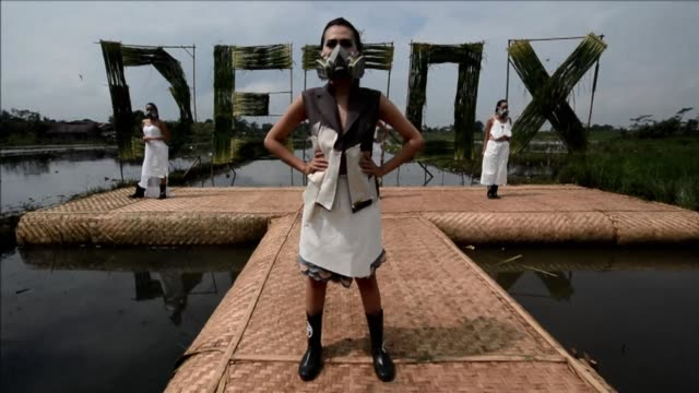 wearing gas masks and designer dresses models parade down a catwalk against a backdrop of polluted rubbish strewn paddy fields in central indonesia a... - ramp stock videos & royalty-free footage