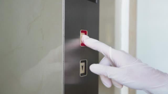 bär handske för att trycka på hissknappen för infektionsförebyggande - hotell bildbanksvideor och videomaterial från bakom kulisserna