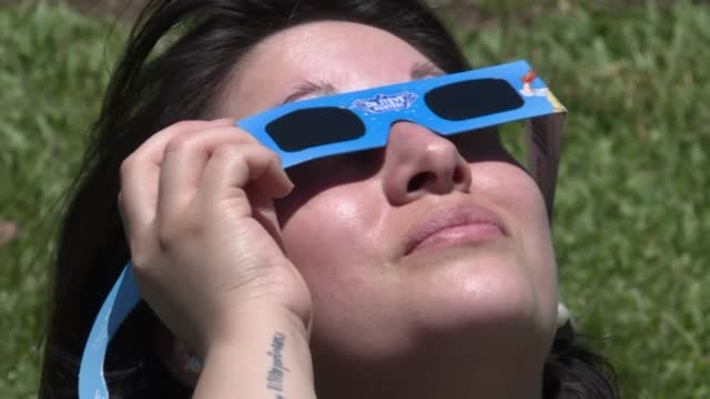 stockvideo's en b-roll-footage met wearing goggles while looking up into the sky, buenos aires residents gather outside the city's galileo galilei planetarium to watch a partial solar... - galileo galilei