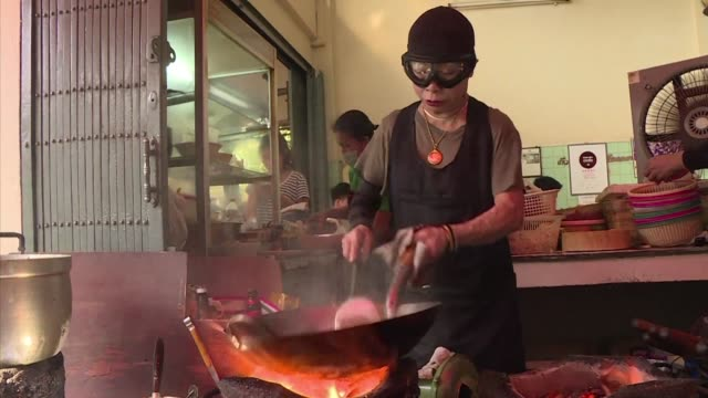 wearing her trademark ski goggles for protection from flying sparks thai cook jay fai hunches over two sizzling woks as tourists from around the... - ski goggles stock videos & royalty-free footage