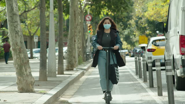 vídeos de stock e filmes b-roll de wearing surgical mask during using electric scooter at barcelona bike path - transportation