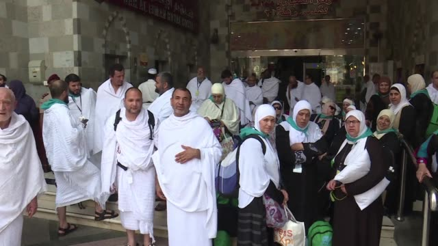 wearing the simple white garb of the pilgrim most of the faithful begin moving from mecca to the nearby mina valley to spend the night there before... - pellegrino video stock e b–roll