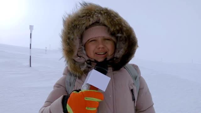 vidéos et rushes de journaliste de temps de parler à la montagne hivernale - reportage
