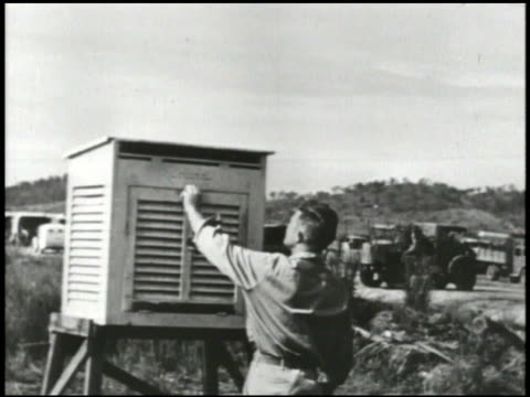 vídeos de stock, filmes e b-roll de 'weather station' sign in unidentified location man opening door of weather box same man climbing wind vane looking at reading wwii world war ii - estação meteorológica