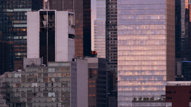 A weather vane sits between a cluster of buildings in Midtown Manhattan