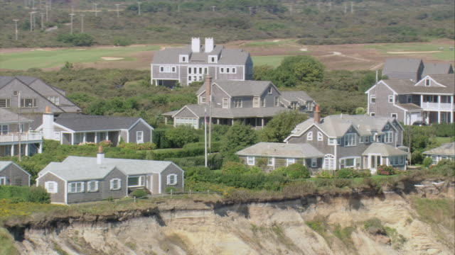 AERIAL Weathered Cape Cod houses with verandas on sandy bluff overlooking shore / Nantucket, Massachusetts, United States