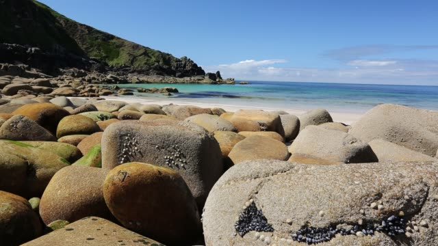 Weathered granite boulders on the beach at Porthmeor Cove, on Cornwall's North Coast, UK.