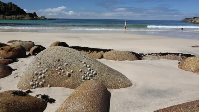 Weathered granite boulders on the beach at Porthmeor Cove, on Cornwall's North Coast, UK, with a woman on the beach.