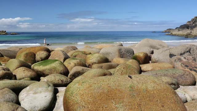 weathered granite boulders on the beach at porthmeor cove, with a woman on the beach, on cornwall's north coast, united kingdom on august 20, 2015. - mineral stock videos & royalty-free footage