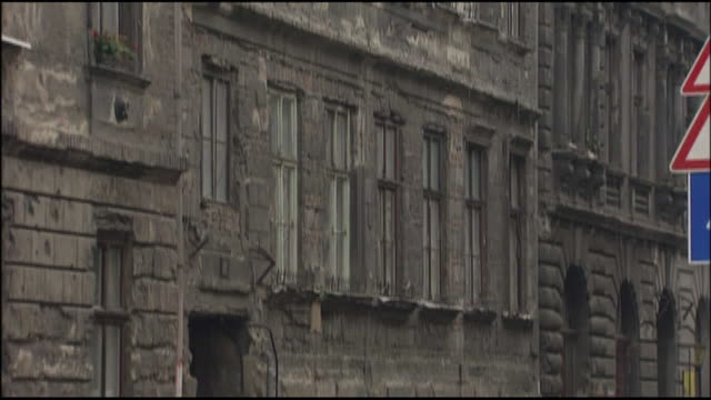 a weathered old stone building lines a neighborhood street in budapest. - weathered stock videos and b-roll footage