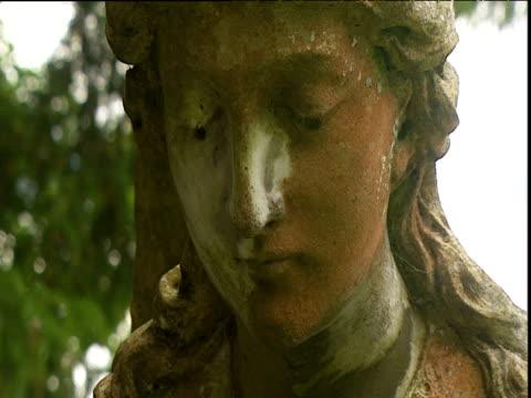 weathered statue of angel in churchyard at cookham berkshire - angel点の映像素材/bロール