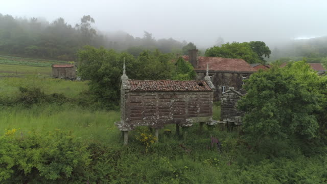 weathered traditional barns amidst plants and houses in village against sky during foggy weather - galicia, spain - temperatur stock-videos und b-roll-filmmaterial