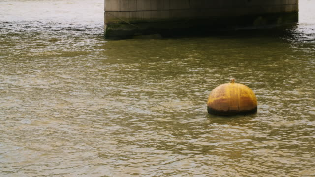 a weathered yellow buoy bobs in the green waters of the river thames - environmental issues stock videos & royalty-free footage