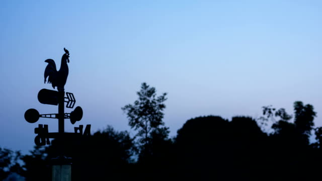 Weathervane moves in the wind at sun rise