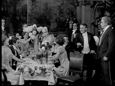 stockvideo's en b-roll-footage met 1909 b/w weathy people at dinner table/ man arriving in tux and toasting with wine glass - 1900 1909