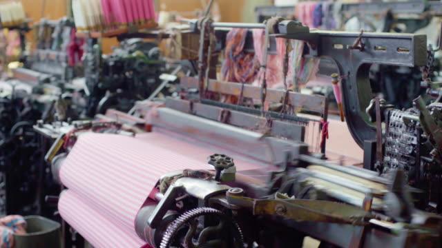 weber maschine retro-stil-threads auf einem loom weben textilstoff in der fabrik. - textilfabrik stock-videos und b-roll-filmmaterial