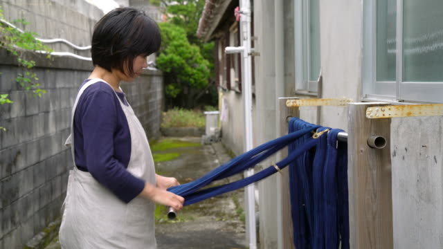 Weaver stretching and drying recently dyed fabric ready for weaving