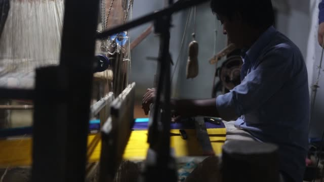vidéos et rushes de a weaver uses a handloom to make a silk saree in a workshop at night in varanasi uttar pradesh india on saturday oct 28 weavers use handlooms to make... - métier à tisser
