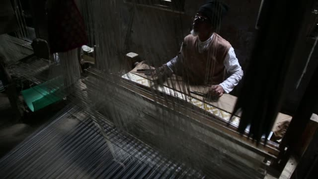 a weaver uses a handloom to make a silk sari at a workshop in varanasi uttar pradesh india on thursday dec 8 close up silk threads are seen during... - sari stock videos and b-roll footage