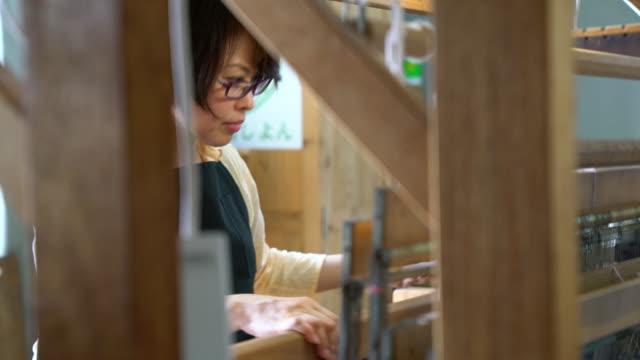 伝統的な日本の織り機を使用しての織工 - オーナー点の映像素材/bロール
