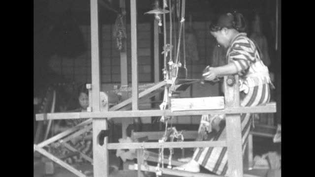 vidéos et rushes de weavers working looms on porch one on floor loom / man working floor loom / closer shot / looms and weavers on porch / woman working loom / weaver at... - tisser
