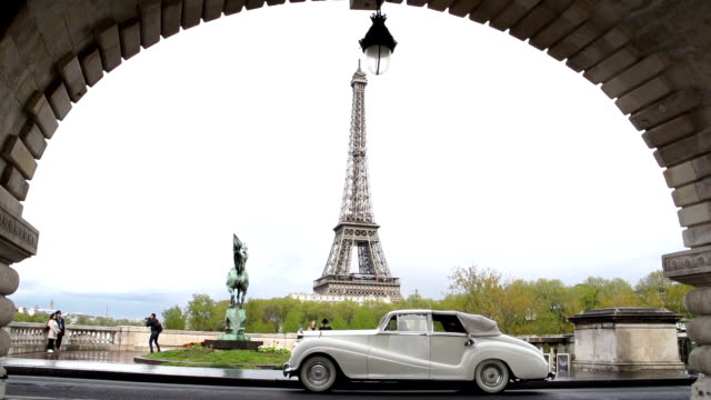 wedding car driving past the eiffel tower, paris. in slow motion - chauffeur stock videos and b-roll footage