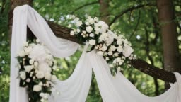 Wedding ceremony arch with hanging flowers and greenery with trees and forest at the background