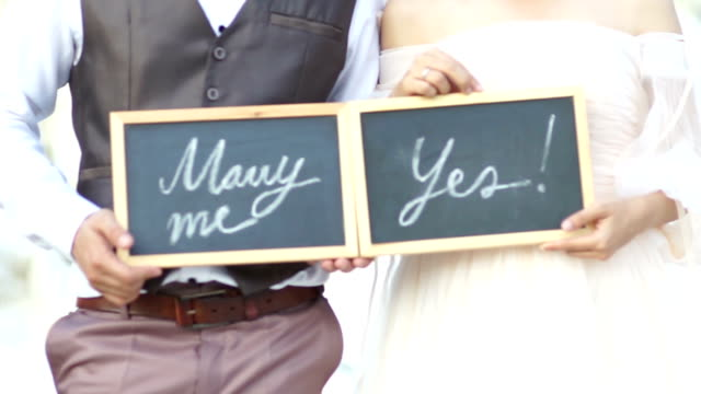 Wedding concept. Will you marry me question and yes, handwritten on blackboard shown by the wedding couple.
