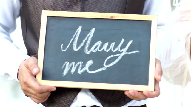 wedding concept. will you marry me question handwritten on blackboard shown by young men. - bride stock videos and b-roll footage
