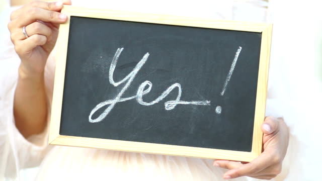 """Wedding concept. Word """"Yes"""" written on blackboard shown by young women."""