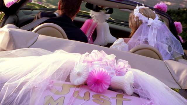 canted rear view wedding couple driving away in 'just married' convertible car - just married stock videos and b-roll footage