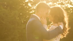 Wedding couple embracing in the striking golden sun light. Slowly