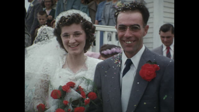 vídeos de stock e filmes b-roll de 1954 home movie wedding couple exiting church, rice thrown, couple posing for picture, wedding party / regina, saskatchewan - casamento