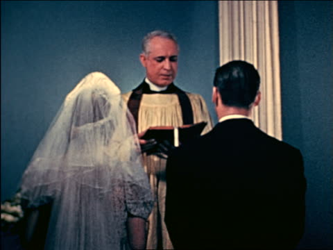 vidéos et rushes de 1941 rear view wedding couple standing as priest performs marriage ceremony / industrial - prêtre
