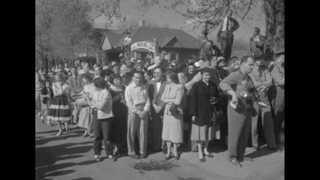 [wedding day 4/21/56] photographers stand behind police barricade and take photos as spectators line street behind them / little girl wearing harness... - sideways glance stock videos & royalty-free footage