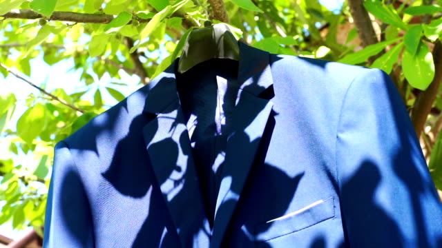 wedding dress of the groom's suit hanging on a tree. - boutique stock videos & royalty-free footage