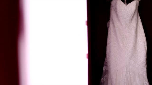 vídeos de stock e filmes b-roll de roupas vestido de casamento de suspensão - vestido branco