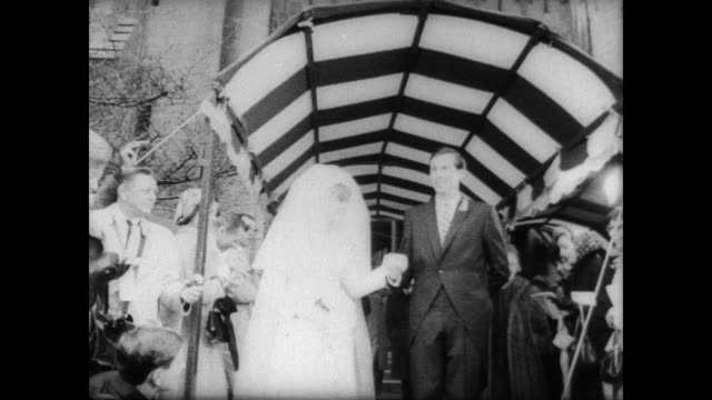 wedding guests crowd either side of a canopy as john d rockefeller iv and his new bride sharon lee percy exit the chapel after their wedding in... - george harrison stock videos & royalty-free footage