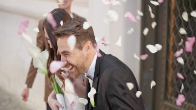 vídeos de stock e filmes b-roll de slo mo ds wedding guests showering newlyweds with rose petals - casamento