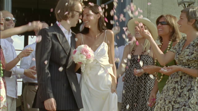 slo mo, ms, cu, wedding guests throwing flower petals on just married couple, chateau du parc, saint ferme, france - just married stock videos and b-roll footage