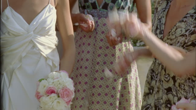 slo mo, cu, wedding guests throwing flower petals on just married couple, mid section, chateau du parc, saint ferme, france - blumenbouqet stock-videos und b-roll-filmmaterial