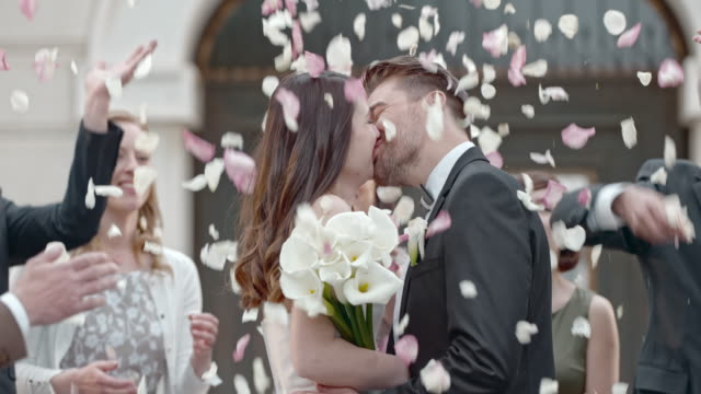 vídeos de stock e filmes b-roll de slo mo wedding guests throwing petals at kissing newlyweds - casamento