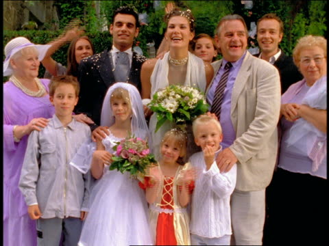 portrait wedding party guests + family standing with bride + groom outdoors / some waving - organised group photo stock videos & royalty-free footage