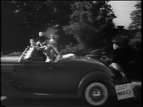 "b/w 1935 wedding party throwing rice at bride + groom as they get into car with ""just married"" sign - just married stock videos and b-roll footage"