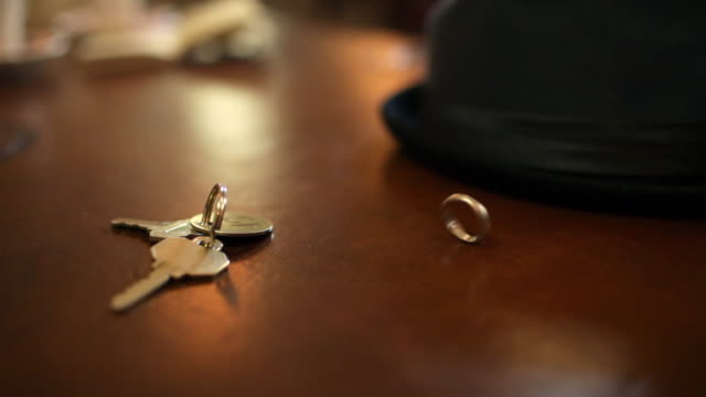 wedding ring spinning on table with hotel key - テーブル点の映像素材/bロール